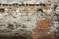 Grunge old bricklaying wall fragment from red bricks and damaged plaster background texture. Close-up Royalty Free Stock Photo
