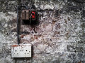 Grunge wall electrical fuse board and socket on a flaking painted Royalty Free Stock Images