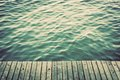 Grunge wood boards of a pier over ocean with rippling waves. Vintage Royalty Free Stock Photo