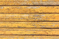 Grunge wood wall with cracks and peeling paint in old house. Yellow textured background