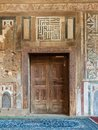 Grunge wooden decorated door on external old decorated marble wall, Cairo, Egypt Royalty Free Stock Photo