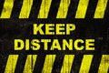 Keep distance text as warning sign with yellow and black stripes on painted wooden wall Royalty Free Stock Photo