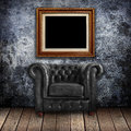 Grungy wall with Classic Brown leather armchair and gold frames Royalty Free Stock Photo