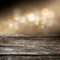 Grungy weathered wooden plank with a background bokeh of defocused twnkling festive party lights on a misty brown background Stock Image