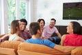 Grupo de amigos que sentam se em sofa watching soccer together Imagens de Stock Royalty Free