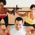 Grupo de la aptitud con el barbell en gimnasia Imágenes de archivo libres de regalías