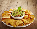 Guacamole dip and nachos plate of on wooden background Royalty Free Stock Photo