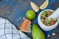 Guacamole - latin american sauce and ingredients avocado, tomatoes, onion, lemon, garlic, lime on blue wooden background. Royalty Free Stock Photo