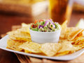 Guacamole in small condiment cup with tortilla chips and beer Stock Photography
