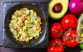 Guacamole in stone mortar and ingredients. Top view Royalty Free Stock Photo