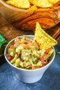 Guacomole is a traditional Mexican sauce consisting of grated avocado, lime juice, red onion, tomatoes, garlic and chili. Served w Royalty Free Stock Photo