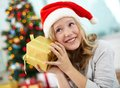 Guessing portrait of happy girl holding giftbox and what is inside on christmas evening Royalty Free Stock Photo