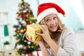 Guessing portrait of happy girl holding giftbox and what is inside on christmas evening Royalty Free Stock Photography