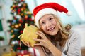 Guessing portrait of happy girl holding giftbox and what is inside on christmas evening Stock Photography