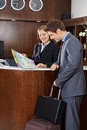 Guest looking at city map with hotel receptionist luggage Royalty Free Stock Photo
