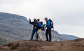 Guide instructs hiking tourists on mountain Stock Photography