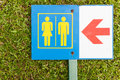Guide post arrow to restroom for men and women on grass Royalty Free Stock Photo