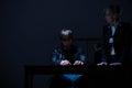Guilty man and policewoman men elderly in dark room Royalty Free Stock Photo