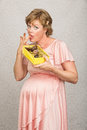 Guilty pregnant woman eating pigging out on box of chocolates Royalty Free Stock Photography