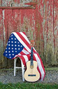 Guitar with american flag by old red barn Royalty Free Stock Images
