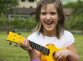 Guitar child happy girl plays yellow Royalty Free Stock Images