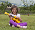 Guitar child happy girl plays yellow Royalty Free Stock Photo