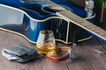 Guitar, money and whiskey on wooden table Royalty Free Stock Photo