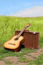 Guitar and old leathern suitcase on the road Royalty Free Stock Photo