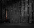 Guitar on old wooden wall a black flap Royalty Free Stock Photography