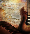 Guitar and piano on brick wall Royalty Free Stock Photo