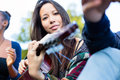 Guitar player girl making music with friends in park Royalty Free Stock Photo