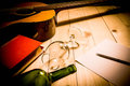 Guitar with Red Book and Wine on a wooden table. Royalty Free Stock Photo