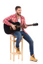The guitarist on a chair singing in red lumberjack shirt sitting play black acoustic guitar studio portrait isolated white Stock Image