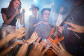 Guitarist performing by crowd at nightclub Royalty Free Stock Photo