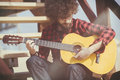 Guitarist with plaid shirt and afro hair Royalty Free Stock Photo