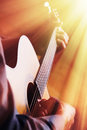 Guitarist playing on acoustic guitar in front of the light Royalty Free Stock Photos