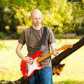 Guitarist young playing guitar in beautiful nature environment Stock Photography