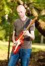 Guitarist young playing guitar in beautiful nature environment Royalty Free Stock Photos