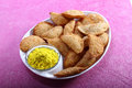Gujia in plate with holi color in bowl indian traditional snack gujiya served along a Royalty Free Stock Photo