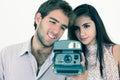 Gulliga par som tar foto med den ögonblickliga gamla kameran Royaltyfri Bild