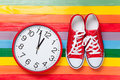 Gumshoes with white shoelaces and clock on multicolor wooden background Royalty Free Stock Photos
