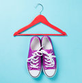 Gumshoes with white shoelaces and red hanger purple on blue background Royalty Free Stock Photos