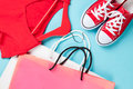 Gumshoes with white shoelaces and shopping bags with dress red on blue background Stock Photography