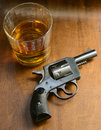 Gun and alcohol with on a rustic wood background Stock Photo