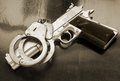 Gun and handcuffs on wooden table Stock Photography