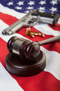 Gun laws a wooden gavel on an american flag with a and bullets in the background focus on the gavel Stock Image
