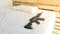 gun Put on a comfortable mattress and pillow white . Royalty Free Stock Photo