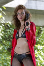 Gun woman in red coat leather bikini and posing outdoor Royalty Free Stock Image