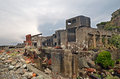 Gunkanjima or hashima is an abandoned islet near nagasaki city completely covered in industrial ruins once a coal mine run by Stock Photo