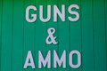 Guns and ammo sign a white cutout letter nailed to a wall of a gun shop advertising for sale Stock Images